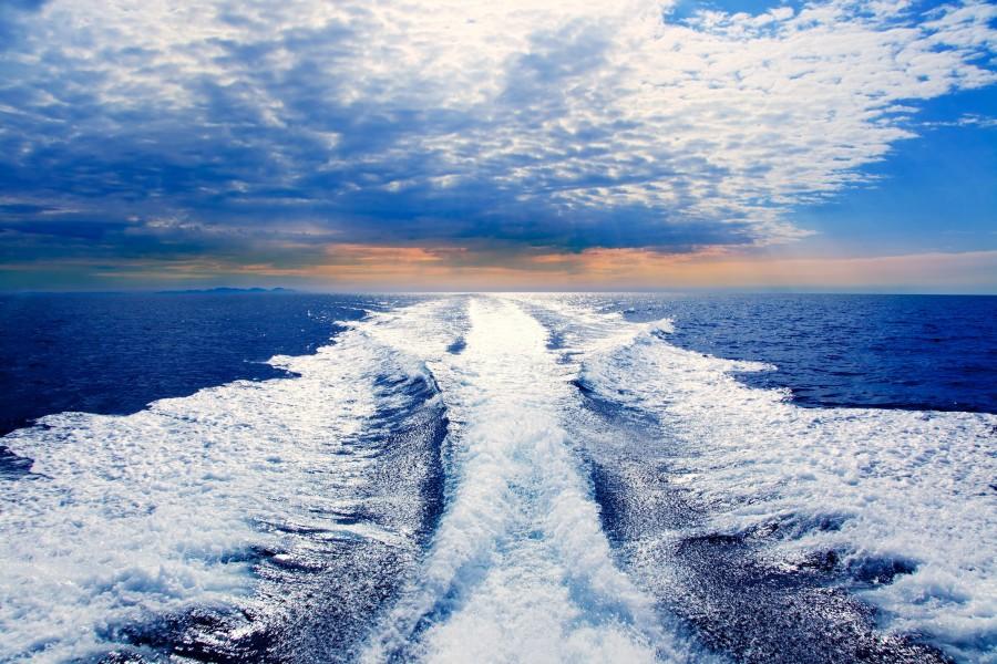 Blue sea with prop wash wake and Ibiza Island in horizon on sunrise